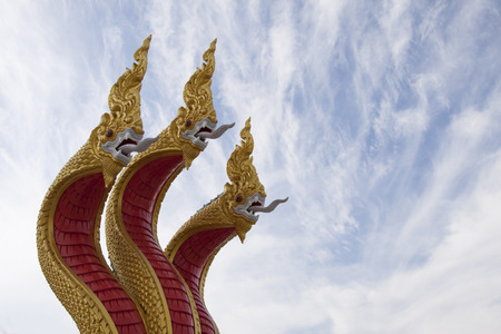 Goden three headed naga statue decorated the stairs leading to Buddha statue Stock Photo