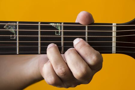 Hand performing D chord on guitar photo