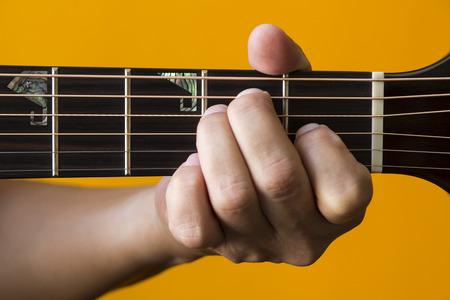e guitar: Hand performing E chord on guitar