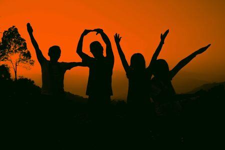 friends: Joyful friends raising hands, silhouette