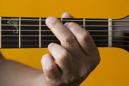 g string: Hand performing G chord on guitar