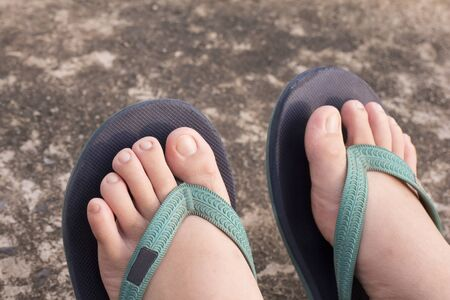 wearing sandals: Feet wearing sandals placed on the cement ground Stock Photo