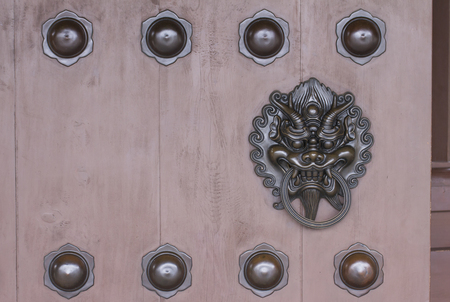 Metal dragon head knocker decorated on the wooden gate of the Chinese temple