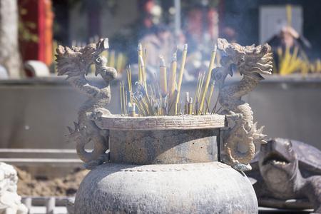 Burning incense stick in dragon decorated censer making smoke