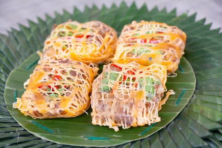 Rhum, Thai traditional food made of minced pork and shrimp fried and wrapped with egg net placed on banana leaf