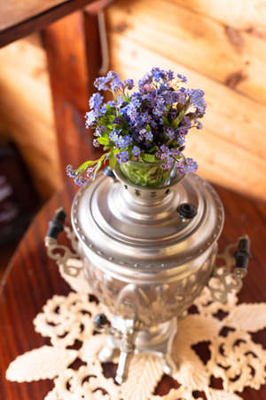 Old metal samovar and a bouquet of blue flowers on a wooden background