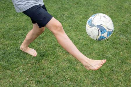 Footballer barefoot stuffs the ball on the green grass.