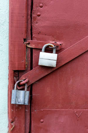 Two gray locks on a burgundy door. Perfect protection.