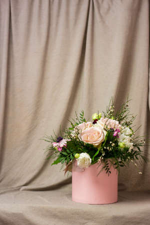 Beautiful bouquets of different colors in a vase on a gray background