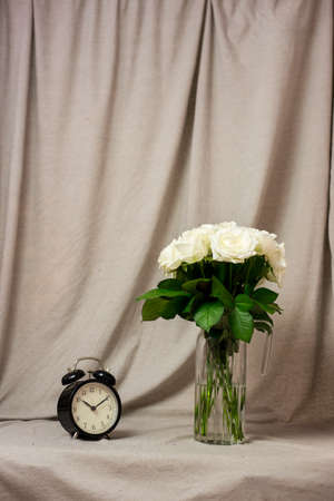 Bouquet of white roses in a vase and a clock on a gray background Imagens
