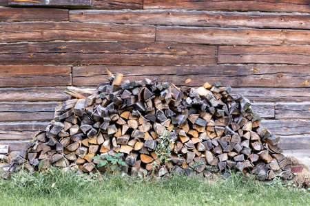 Firewood stacked near wooden brown wall Stok Fotoğraf