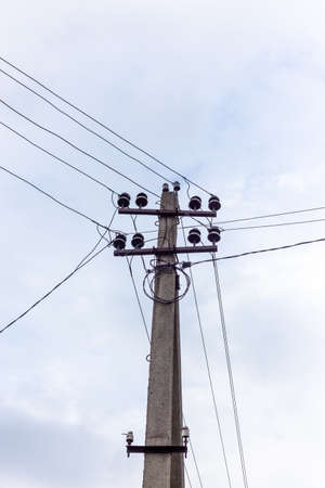 Electric pole and wires against the sky