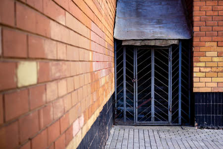 The entrance to the basement is closed with a steel grate