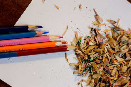 Colored pencils and shavings after sharpening pencils on a white sheet Stockfoto