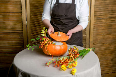 Florist at work: How to make a Thanksgiving centerpiece with big pumpkin and bouquet of flowers. Step by step, tutorial. Foto de archivo