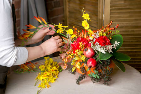 Florist at work: How to make a Thanksgiving centerpiece with big pumpkin and bouquet of flowers. Step by step, tutorial. Stockfoto