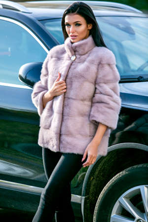 A beautiful brunette in a light-colored fur coat and black trousers is standing near a car on an autumn sunny day, looking sexually at the camera
