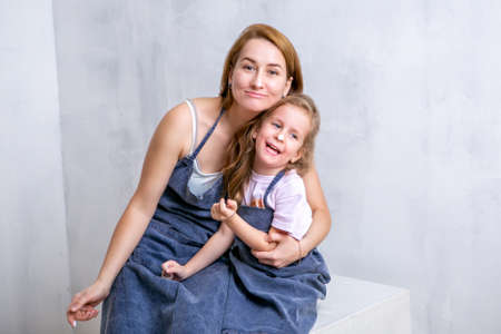 Repair in the apartment. Happy family mother and daughter in aprons paint the wall with white paint. Mother and daughter smeared each other with paint and laugh Stock fotó