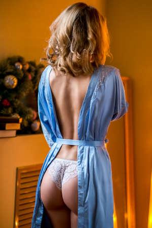 Jeune fille blonde mince en lingerie et boudoir debout près du rebord de la fenêtre et du pompon. Vue arrière. Photo verticale Banque d'images