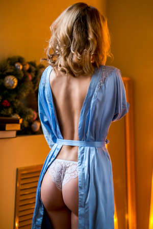 Young slim sexy blond girl in lingerie and boudoir standing near windowsill and primp. Back view. Vertical photo Foto de archivo