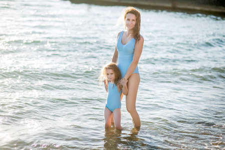 Beautiful young mother and daughter having fun resting on the sea. They stand in the water in the same swimsuit and smile. Horizontal photo 版權商用圖片