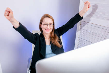 Portrait of happy young successful businesswoman celebrate something with arms up at office. Positive emotion. Big deal, promotion, lottery win or discount concept. Black Friday or Cyber Monday. Stock Photo