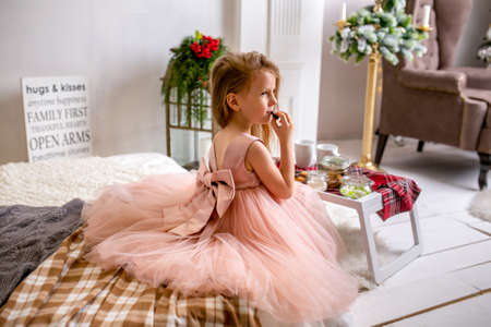 Pretty little girl 4 years old in a pink dress. Child in the Christmas room with a bed, eating candy, chocolate, cookies and drinking tea, feeding teddy bears and laughing, good mood.
