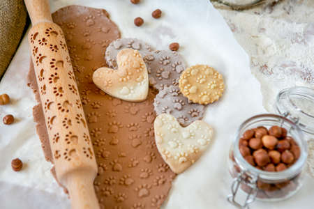 Rolling pin with a dog paw pattern on a wooden decorated table covered with baked flour. Rolled dough with a pattern and cookie of various shapes. Biscuit cooking background, close-up.