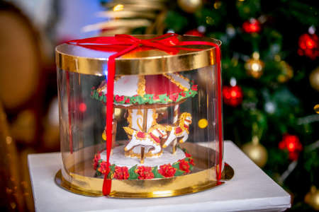Gingerbread carousel in a gift box in front of defocused lights of Chrismtas decorated fir tree. Holiday sweets. New Year and Christmas theme. Festive mood.
