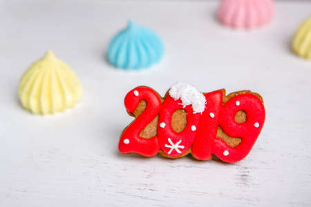 Gingerbread in the form of a numbers 2019 and meringue on a white vintage background. Holiday sweets. New Year and Christmas theme. Festive mood. Christmas card.