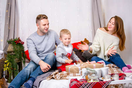 Happy family, father, mother and son, in the morning in bedroom decorated for Christmas. They open presents and have fun. New Year's and Christmas theme. Holiday mood.