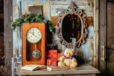 Teddy bear, gifts, books, vintage clock and mirror on a wooden background in the room decorated for Christmas. Holiday mood. Happy New Year theme. Christmas Card. Banque d'images - 111681341