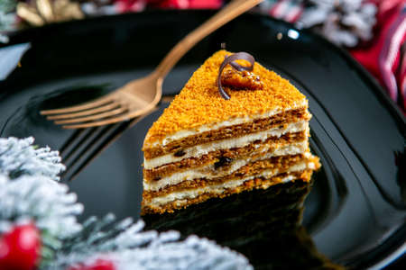 Delicious biscuit cake with nuts on topping. Tasty dessert food in close up. Dessert served on black plate, decorated fir branches. French cuisine. Christmas theme. Imagens