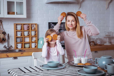 Happy little girl and her beautiful young mother have breakfast together in a white kitchen. They are having fun and playing with cookies. Maternal care and love.