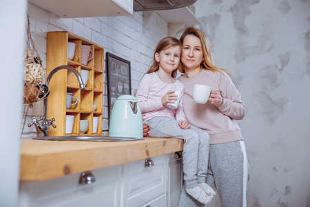 Happy little girl and her beautiful young mother have breakfast together in a white kitchen. They hug and drink tea. Maternal care and love. Horizontal photo.