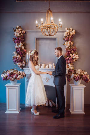 Portrait of happy young bride and groom in a classic interior near the fireplace with flowers. Wedding day, love theme. First day of a new family.