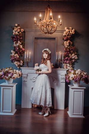 Portrait of happy young bride in a classic interior near the fireplace with flowers. Wedding day, love theme. First day of a new family.