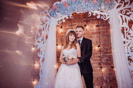 Portrait of happy young bride and groom in a classic interior near the wedding arch with flowers. Wedding day, love theme. First day of a new family.