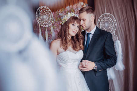 Portrait of happy young bride and groom in a classic interior near the dream catchers. Wedding day, love theme. First day of a new family.