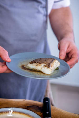 Cook holds a plate of stewed halibut. Master class in the kitchen. The process of cooking. Step by step. Tutorial. Close-up. Stock Photo