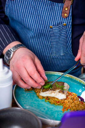 Chef decorates the halibut stewed in mango sauce. Master class in the kitchen. The process of cooking. Step by step. Tutorial. Close-up.
