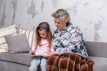 Grandmother and her little granddaughter are watching movies together and playing on the tablet while sitting on the sofa. Grandmom hugs granddaughter. Maternal care and love. Horizontal photo. 스톡 콘텐츠