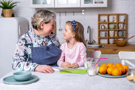 Happy little girl and her grandmother have breakfast together in a white kitchen. They are having fun and playing with fruits. Maternal care and love. Healthy eating.