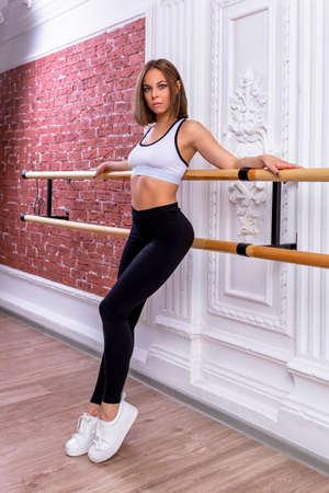 Junges schönes flexibles Mädchen in weißem bauchfreiem Top und schwarzen Leggings posiert im Tanzstudio. Stretching und Bodyballett-Thema. Moderner Tanztrend. Trainer leitet Meisterklasse. Standard-Bild