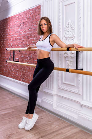 Young beautiful flexible girl in white crop top and black leggings is posing in dance studio. Stretching and body ballet theme. Modern dance trend. Trainer conducts master class. Imagens