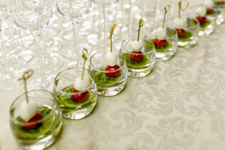 the buffet at the reception. Glasses of wine and champagne on background. Assortment of canapes in glass cups. Banquet service. Catering food, snacks with cheese and small tomatoes.