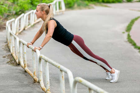 Fitness lifestyle. Young woman doing push ups in the slope. Sporty young blonde girl on a sunny day at the stadium. Healthy life concept. Horizontal photo.