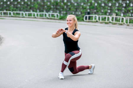Fitness lifestyle. Young woman doing side lunges with a turn. Workout at the stadium. Healthy life concept.