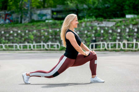 Fitness lifestyle. Young woman doing lunges to the side. Workout at the stadium. Healthy life concept. Horizontal photo.