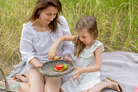 Beautiful young mother and her little daughter in white dress having fun in a picnic. They are sitting on a plaid on the grass, little girl puts vegetables on bread. Maternal care and love.